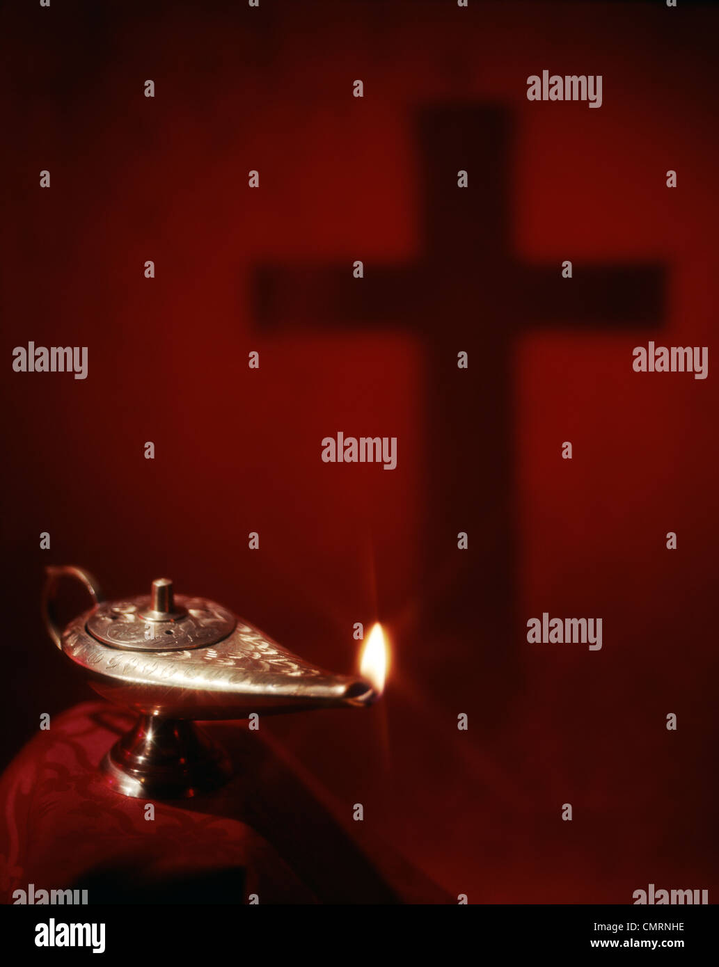 FLAME IN BRASS LAMP OF KNOWLEDGE AND SHADOW OF CROSS ON RED BACKGROUND - Stock Image