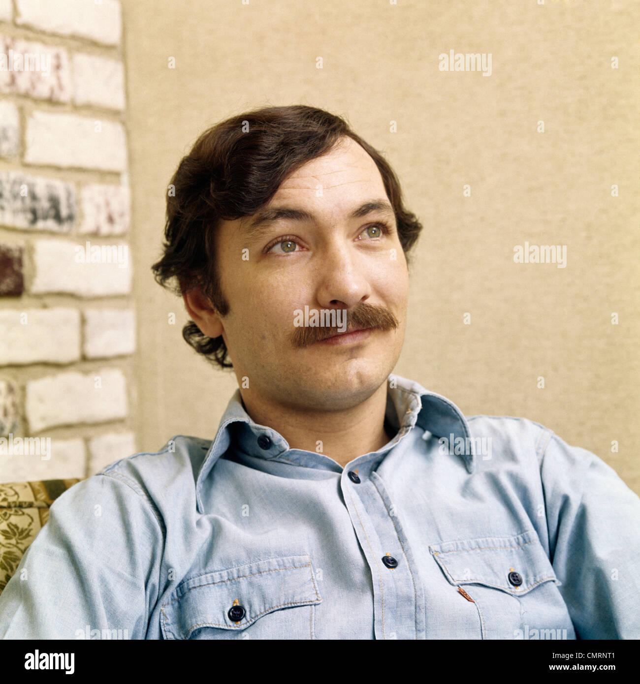 1970 1970s RETRO PORTRAIT MAN WITH BROWN HAIR MOUSTACHE WEARING DENIM SHIRT - Stock Image