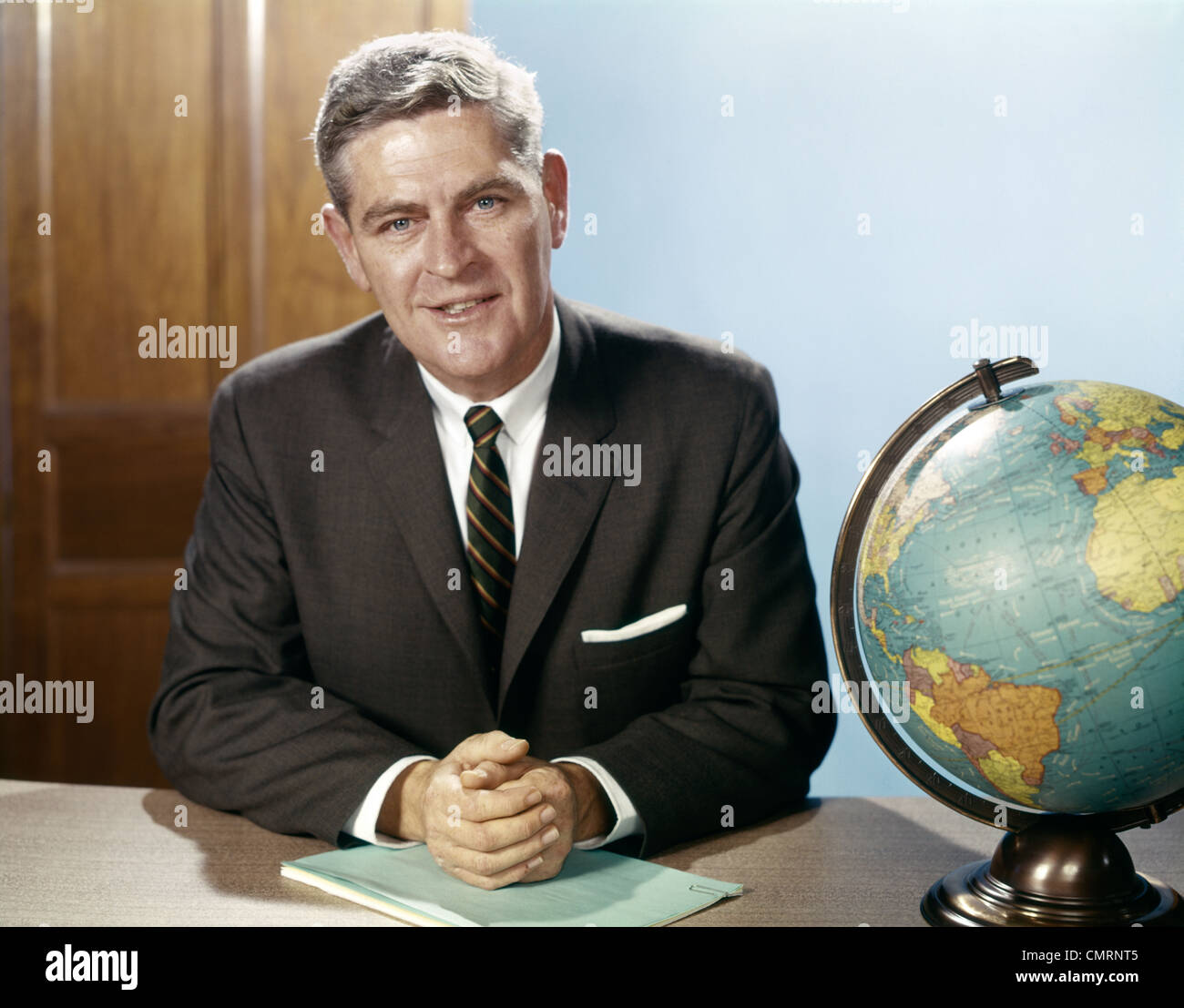 PORTRAIT MAN BUSINESSMAN SITTING AT DESK NEXT TO GLOBE OF THE EARTH OFFICE INDOOR - Stock Image