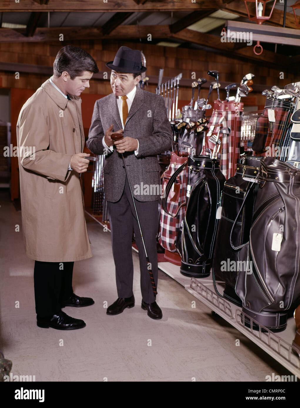 TWO MEN IN GOLF EQUIPMENT SHOP TALKING AND DISCUSSING PURCHASE OF A DRIVER GOLF CLUB - Stock Image