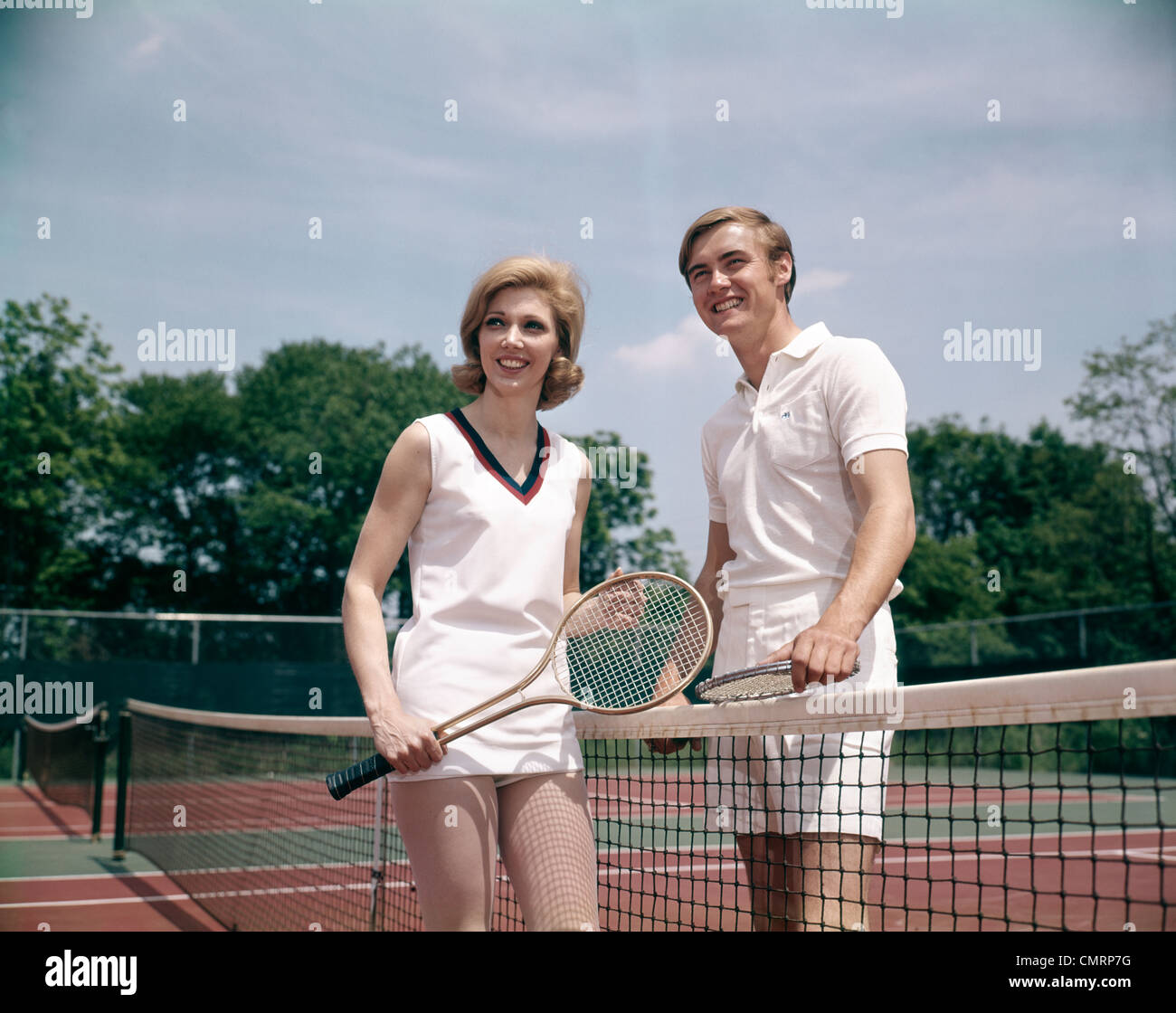 1970 1970s RETRO SMILING COUPLE MAN WOMAN STANDING ON OPPOSITE SIDES OF NET TENNIS COURT HOLDING RACKETS RECREATION - Stock Image