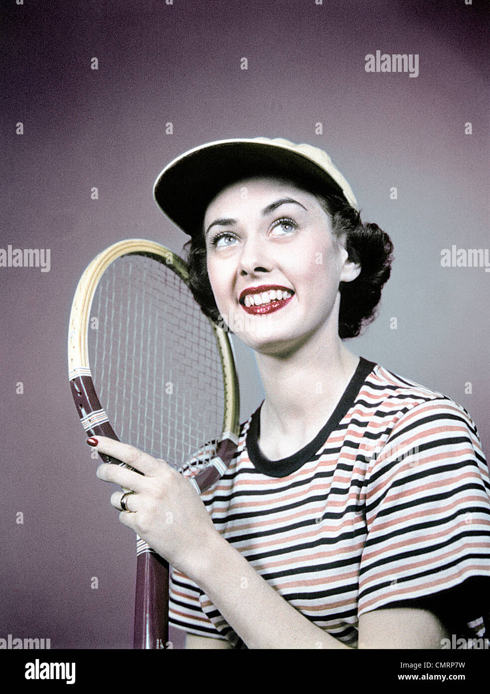 1950s SMILING BRUNETTE WOMAN HOLDING TENNIS RACKET WEAR STRIPED SHIRT CAP - Stock Image