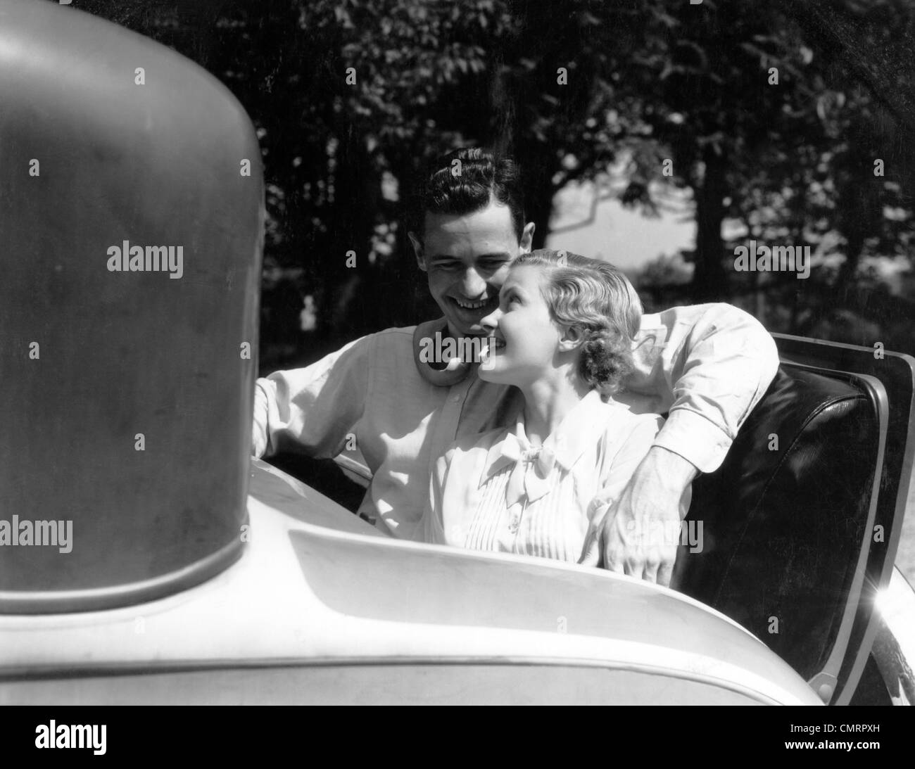 1930s COUPLE IN BACK RUMBLE SEAT REAR OF CAR MAN WITH ARM AROUND WOMAN - Stock Image