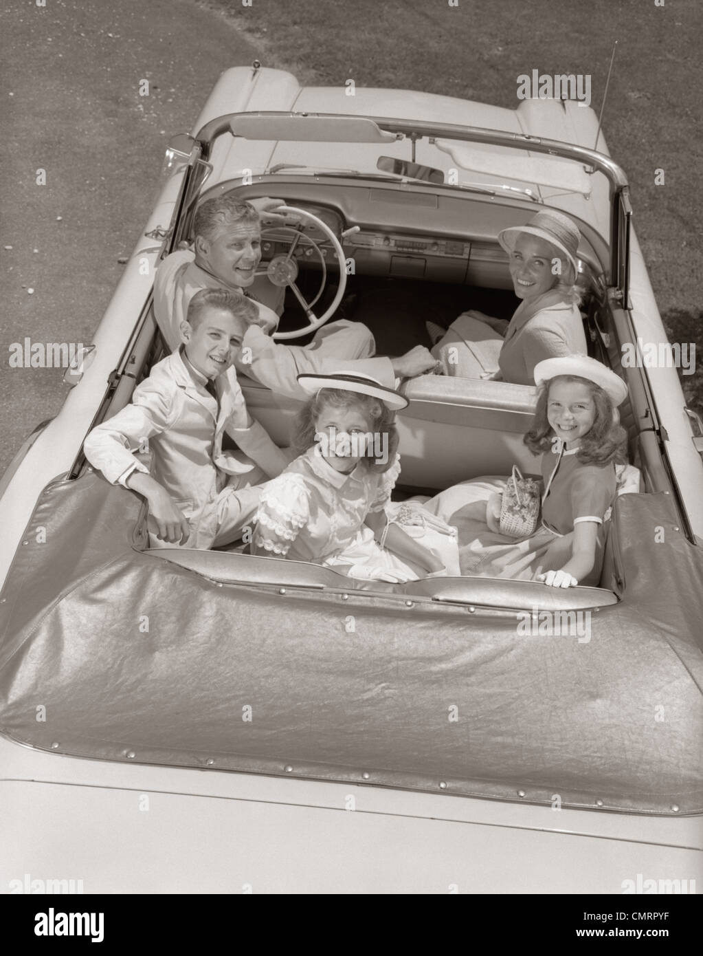 1960s FAMILY PORTRAIT FATHER MOTHER SON TWO DAUGHTERS IN CONVERTIBLE CAR OUTDOOR LOOKING UP AT CAMERA - Stock Image