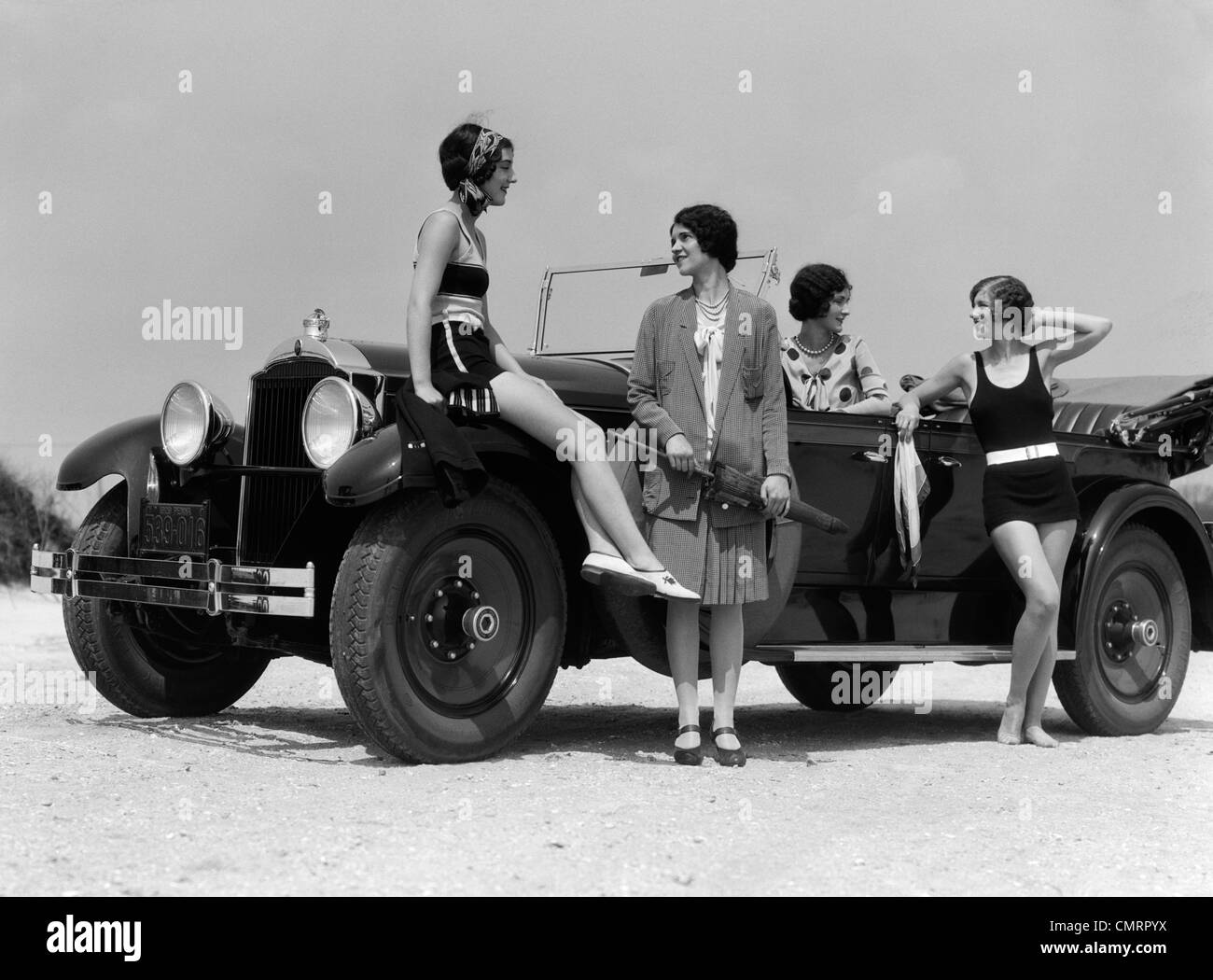 1920s 1930s FOUR WOMEN AROUND CONVERTIBLE TOURING CAR AT SEASHORE TWO IN BATHING SUITS & TWO DRESSED FOR FASHION Stock Photo