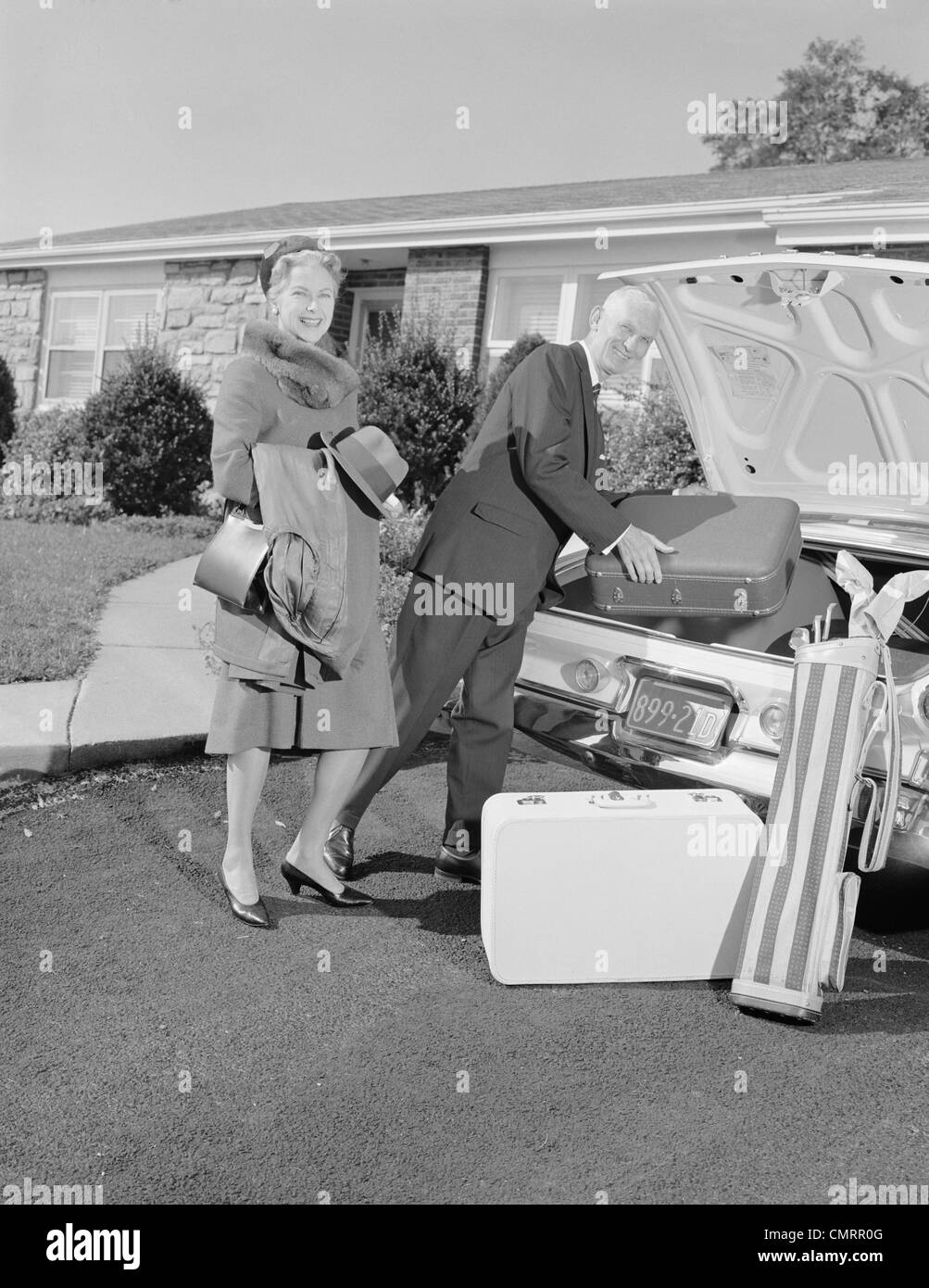 1960s SENIOR MAN WOMAN HUSBAND WIFE PACKING TRUNK WITH LUGGAGE - Stock Image