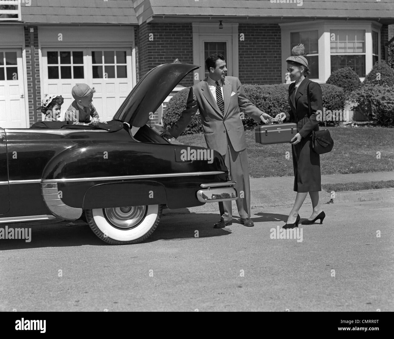 1950s HUSBAND AND WIFE PACKING TRUNK OF CONVERTIBLE WITH LUGGAGE WHILE SON & DAUGHTER WATCH FROM BACK SEAT - Stock Image