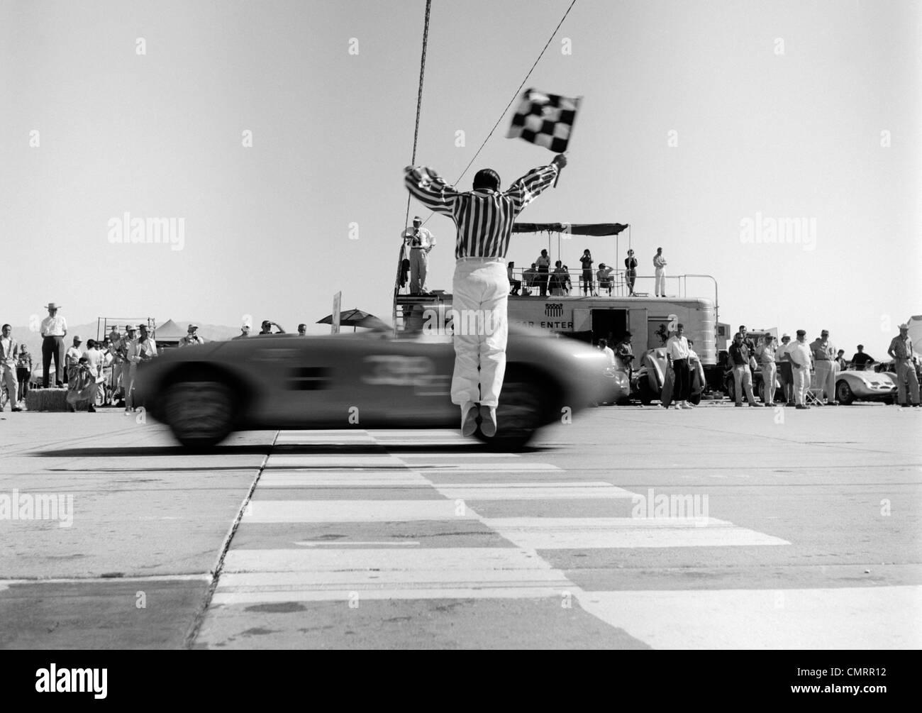 1960s Man Jumping Waving Checkered Flag As Winning Sports Car Stock