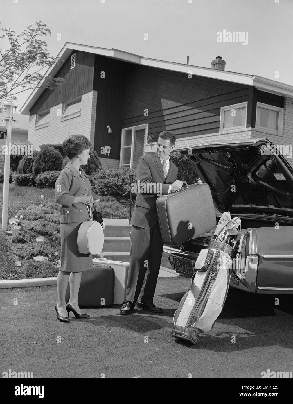 1960s COUPLE MAN WOMAN PACKING LUGGAGE INTO CAR TRUNK BY SUBURBAN HOUSE - Stock Image