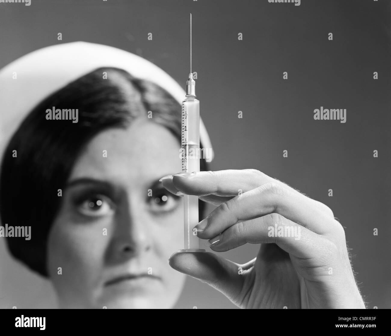 1960s NURSE ADJUSTING DOSAGE INJECTION HYPODERMIC NEEDLE - Stock Image