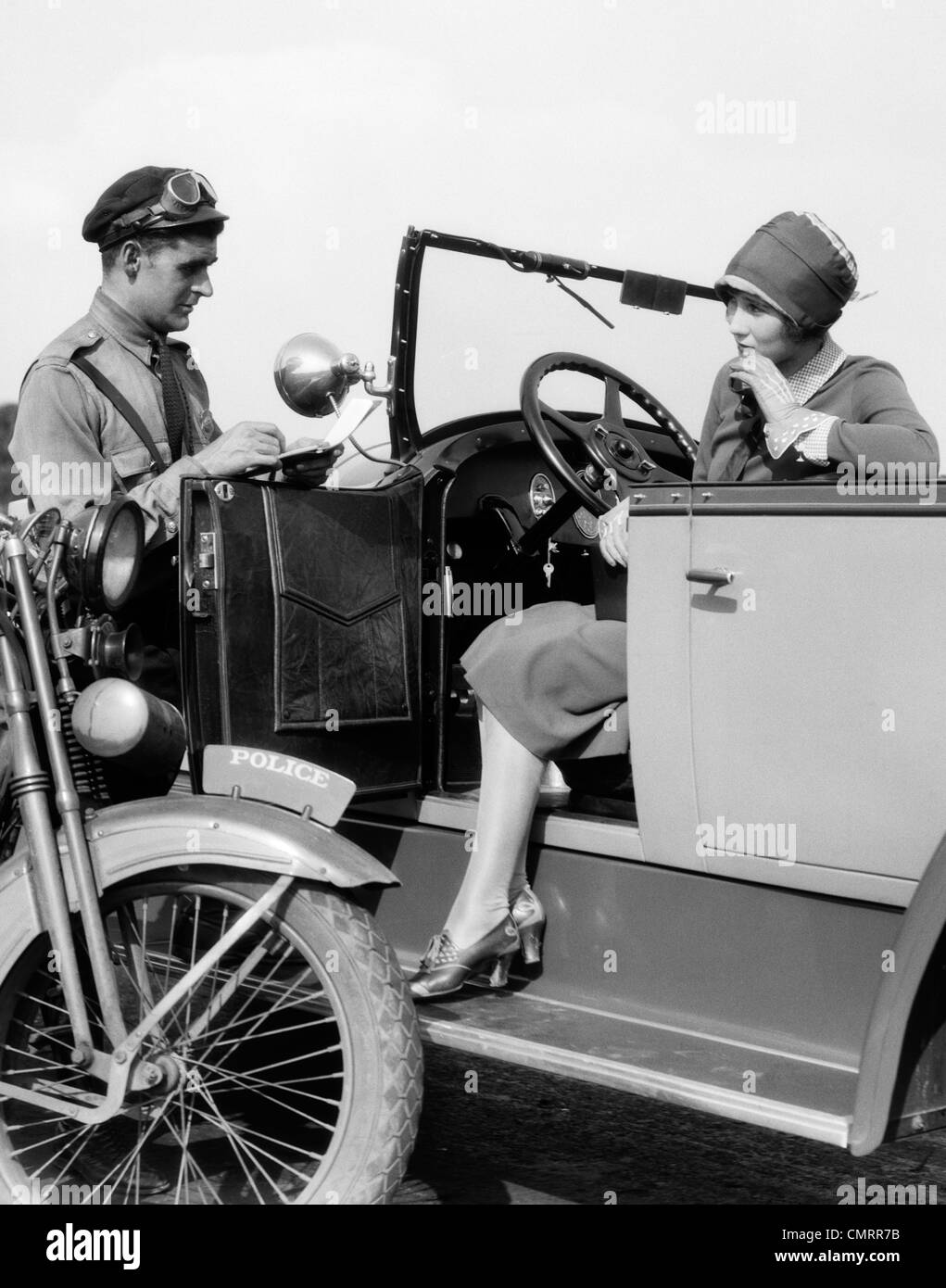 1920s WOMAN IN CAR GETTING TICKETED BY MOTORCYCLE COP - Stock Image