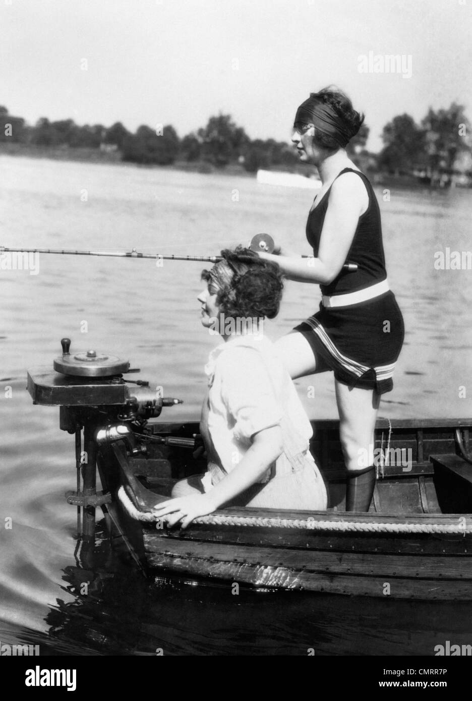 1920s 1930s TWO WOMEN FISHING FROM STERN OF SMALL BOAT WITH MOTOR OUTDOOR ONE WOMAN WI WEARING BATHING SUIT - Stock Image