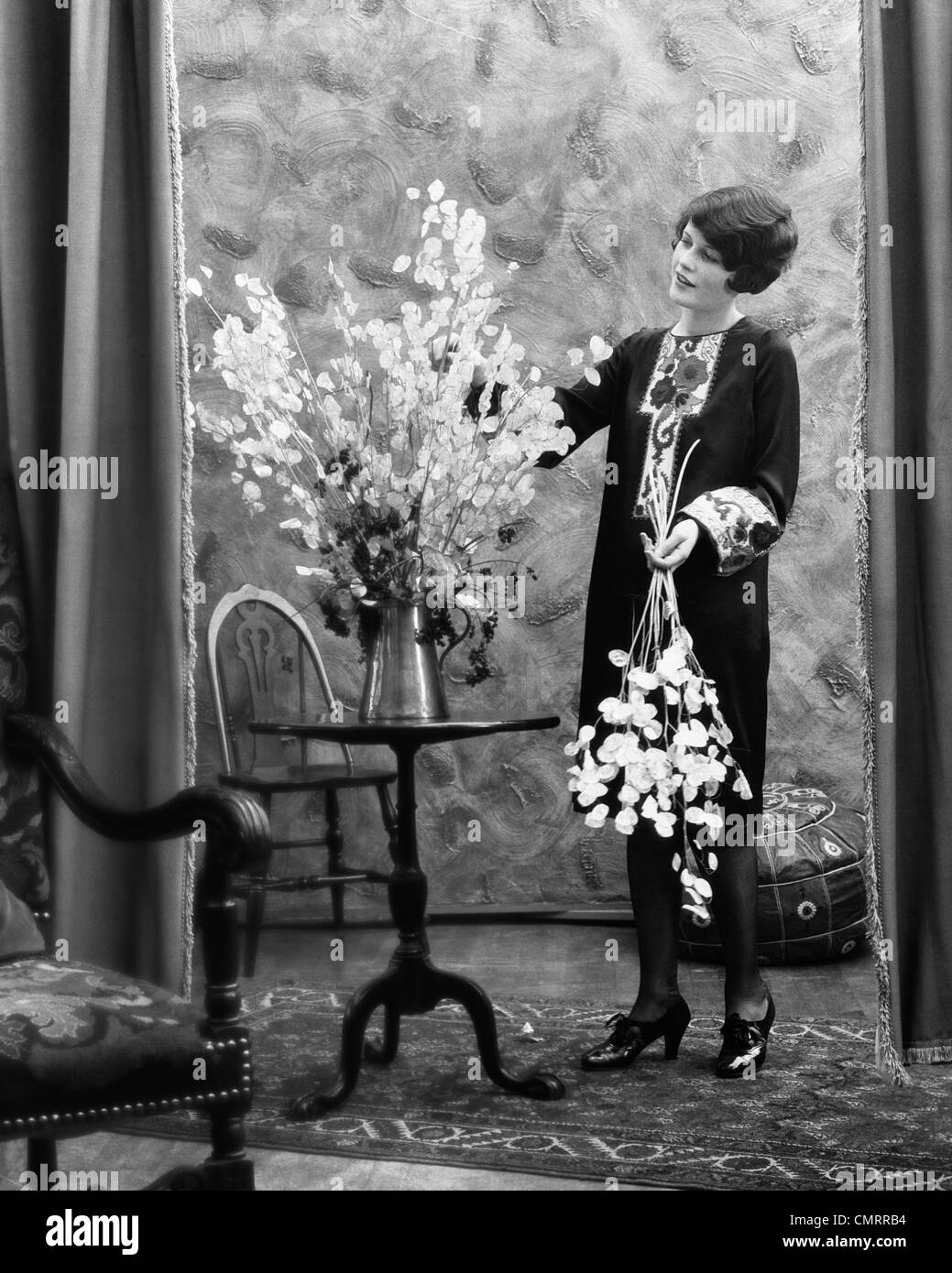 1920s WOMAN ARRANGING FLOWERS IN ALUMINUM PITCHER - Stock Image