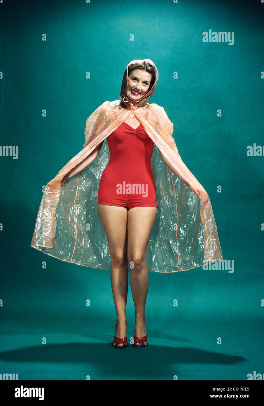 9907d3e43f1fc 1950s SMILING WOMAN PINUP WEARING RED ONE PIECE BATHING SUIT RAIN CAPE  LOOKING AT CAMERA -