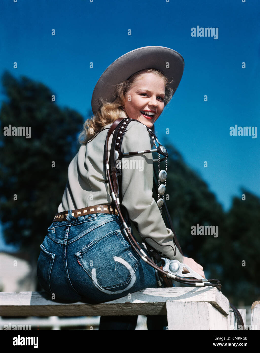 1940s 1950s SMILING BLOND WOMAN WEARING WESTERN COWGIRL CLOTHES LOOKING  OVER SHOULDER SITTING ON WOODEN FENCE c92086fc5a66