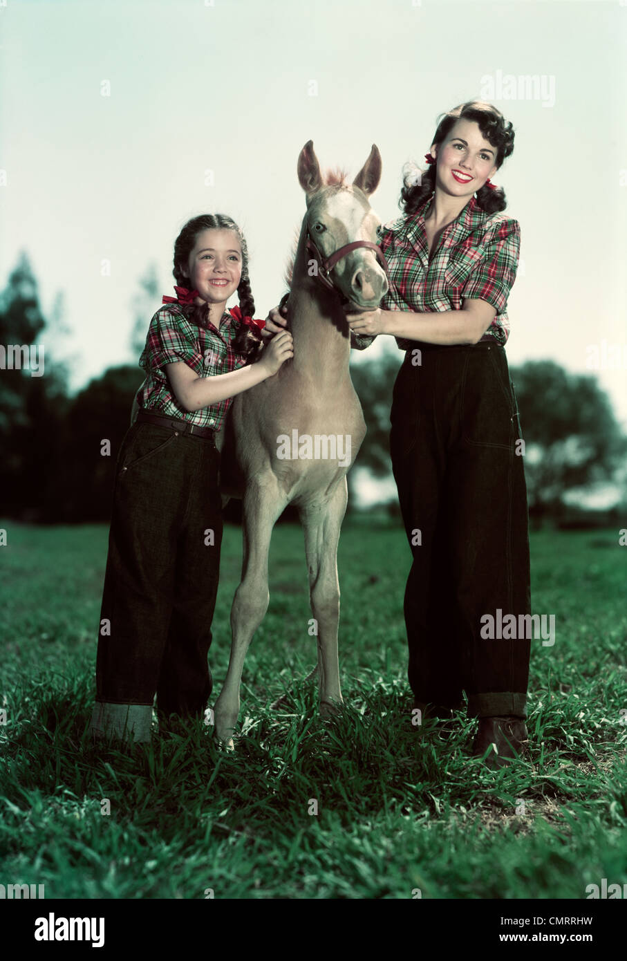 1940s 1950s SMILING GIRL AND TEENAGE GIRL WEARING MATCHING PLAID SHIRTS AND JEANS POSING WITH PONY COLT - Stock Image