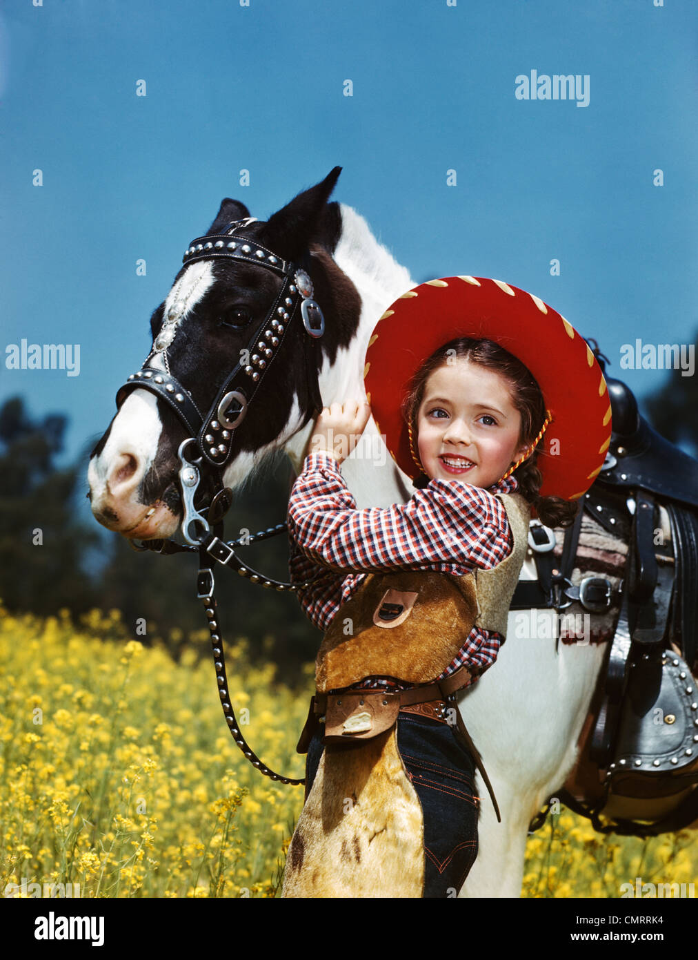 1940s 1950s SMILING GIRL WEARING COWGIRL OUTFIT COWBOY HAT PETTING BLACK AND WHITE PONY - Stock Image