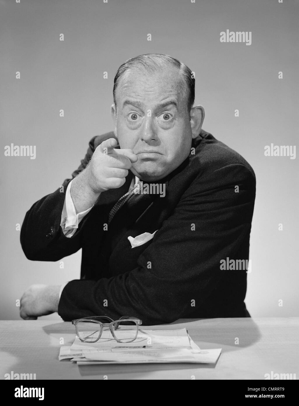 1950s 1960s ANGRY BUSINESSMAN POINTING FINGER BULGING STARING EYES WIDE OPEN - Stock Image
