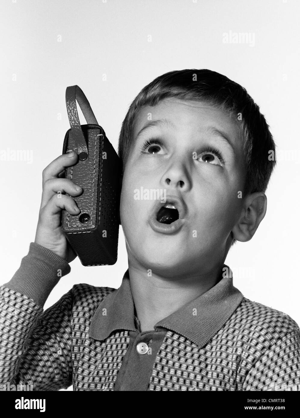1960s BOY HOLDING TRANSISTOR RADIO UP TO HIS EAR WHILE HE SINGS ALONG - Stock Image