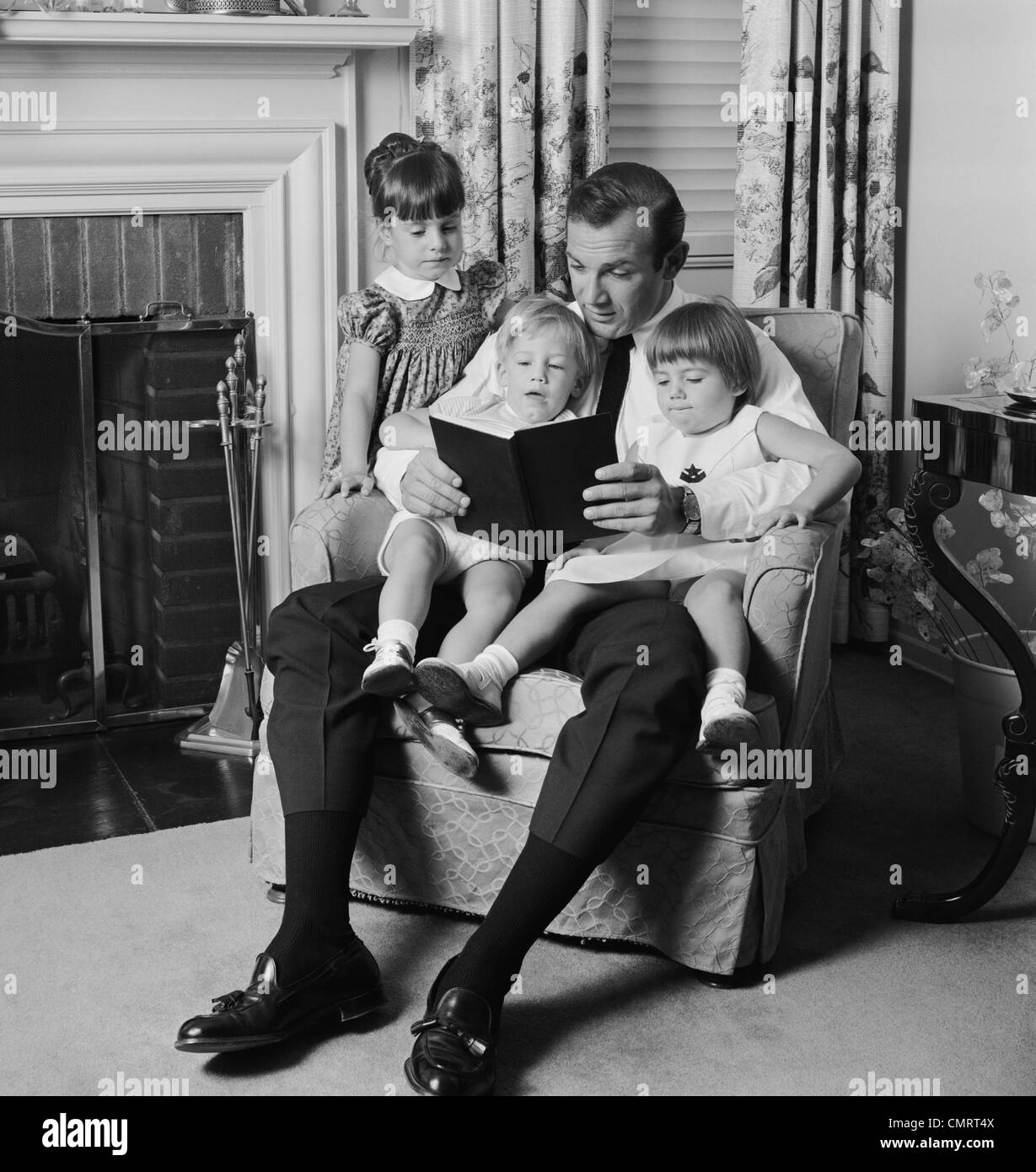 1970s MAN FATHER SITTING IN CHAIR WITH THREE CHILDREN READING BOOK - Stock Image
