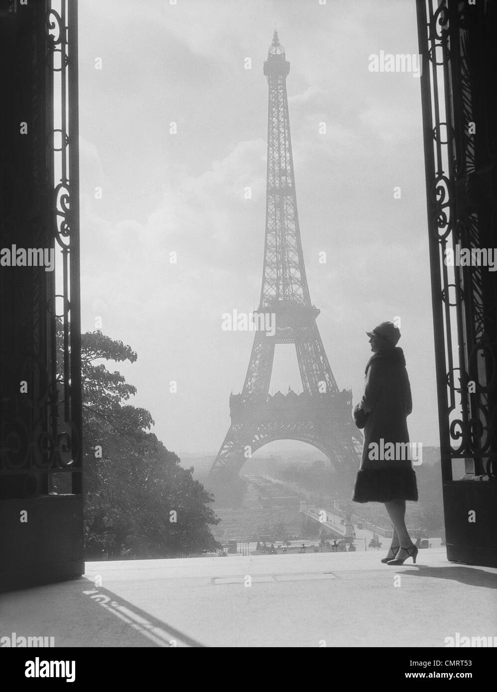 1920s 1930s MOODY SILHOUETTED WOMAN PARIS STANDING IN TROCADERO LOOKING TOWARD EIFFEL TOWER - Stock Image
