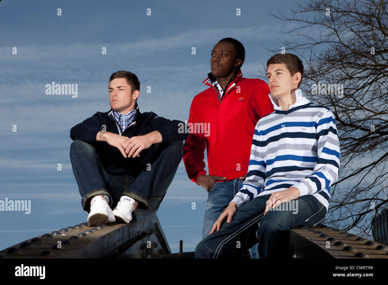 Three young men in their early twenties / late teens sitting and looking into the distance. - Stock Image