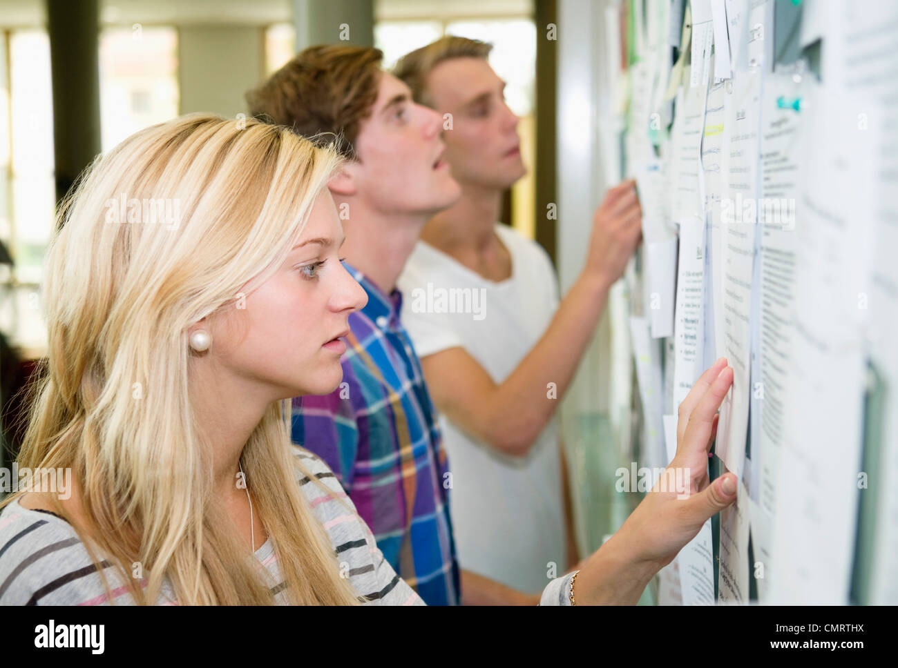 Three students standing by notice board - Stock Image