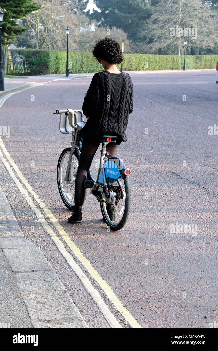 Female cyclist on a Barclays bike on empty road, Inner Circle, Regent's Park, London England UK - Stock Image