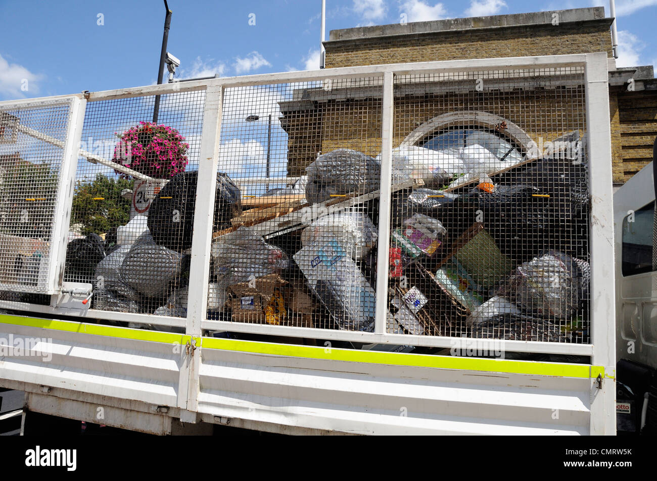 Vehicle with mesh panels on the side containing rubbish bags - Stock Image