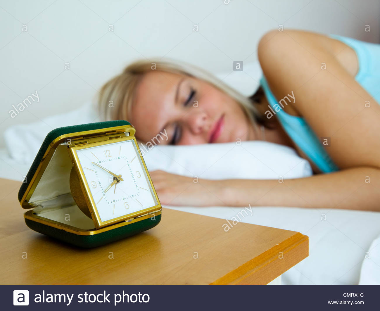 Girl sleeping next to alarm clock - Stock Image