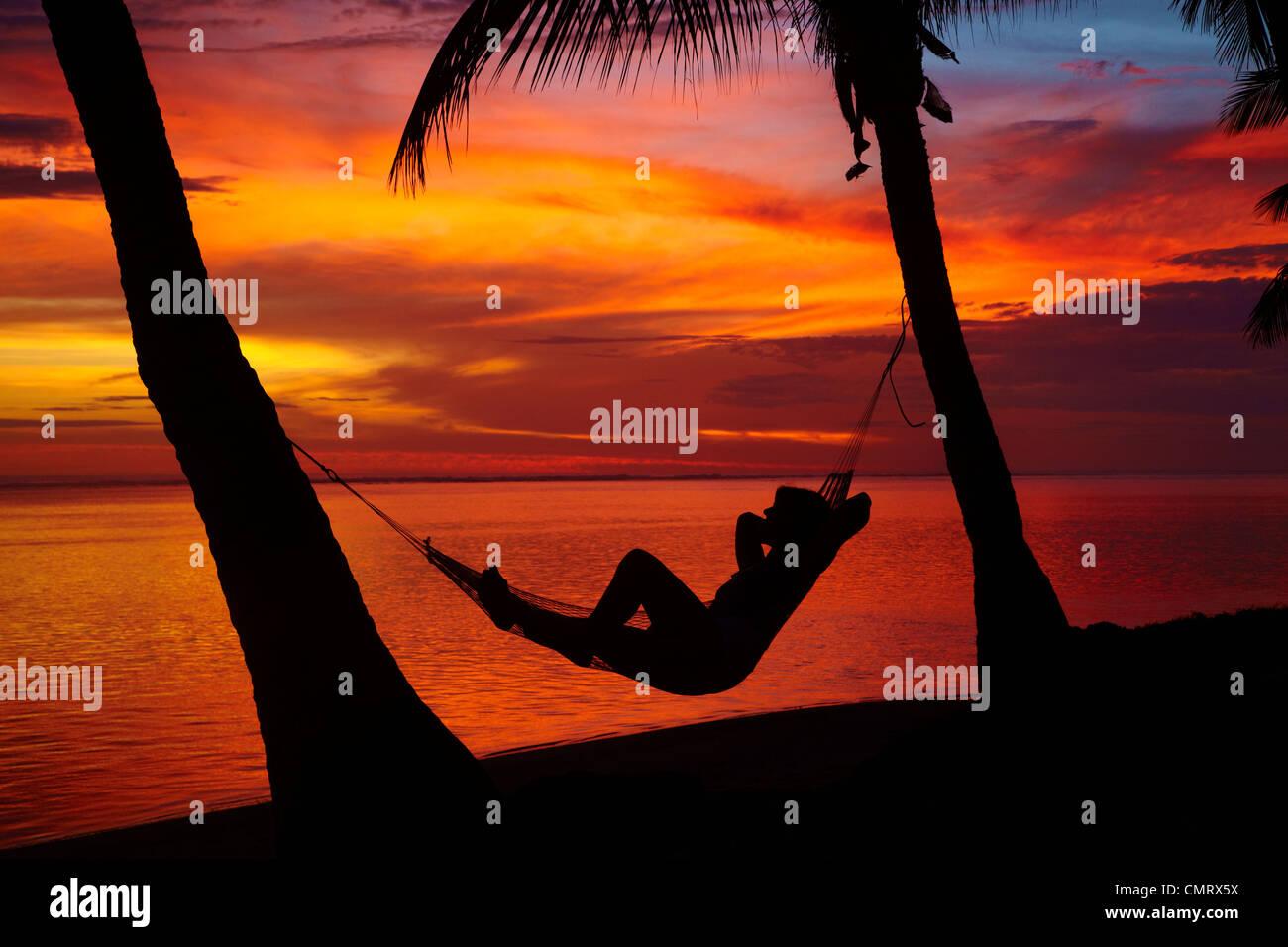 Woman in hammock, and palm trees at sunset, Coral Coast, Viti Levu, Fiji, South Pacific - Stock Image