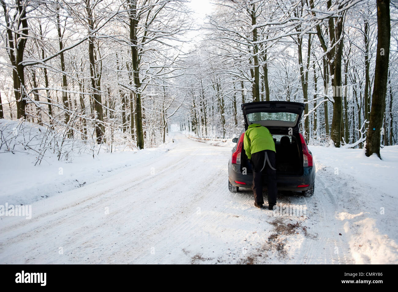 Man packing boot on winter road - Stock Image