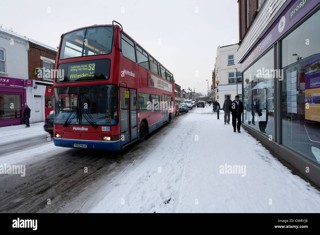 A red double decker bus driving in snow near Willesden Green, London. - Stock Image