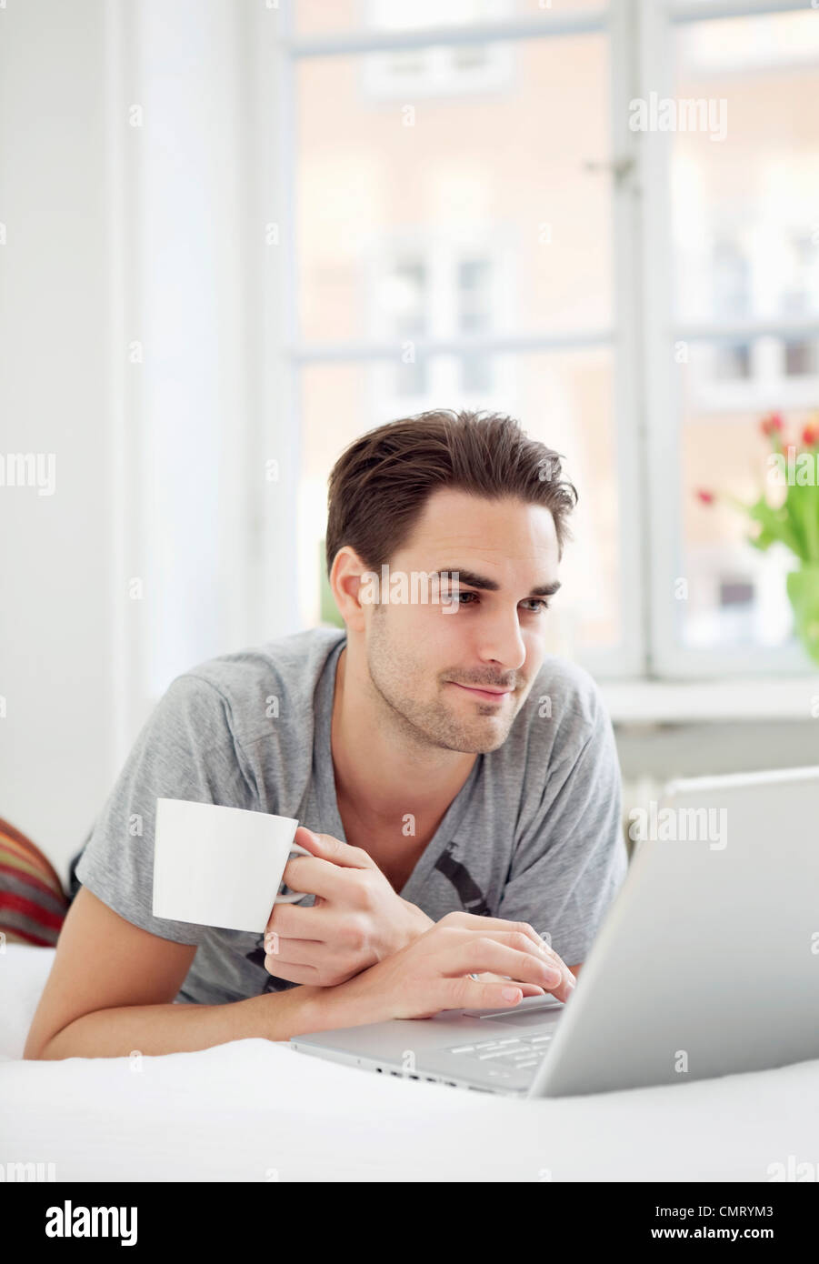 Man with coffee and computer - Stock Image