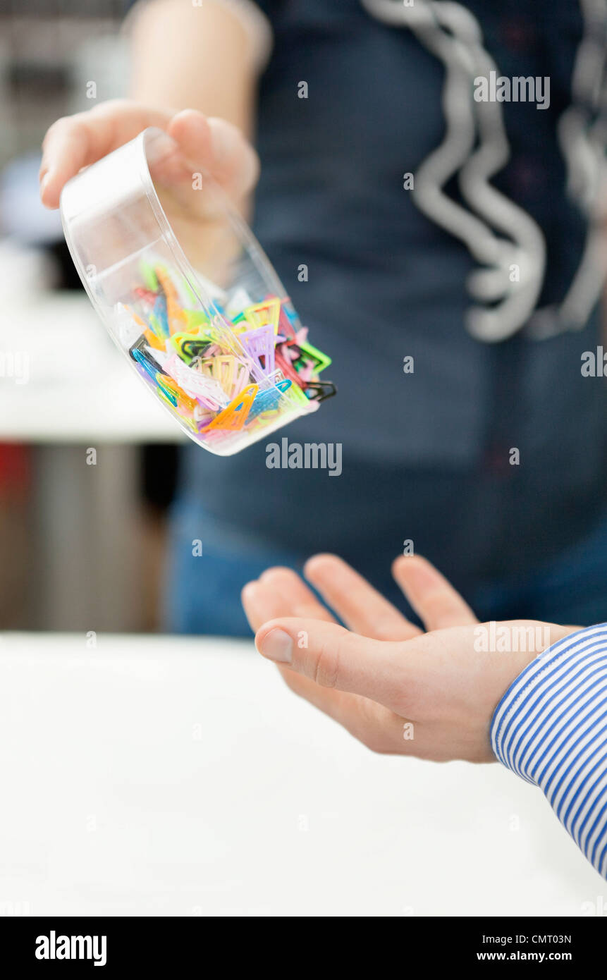 Woman pouring paper clips into mans hand - Stock Image