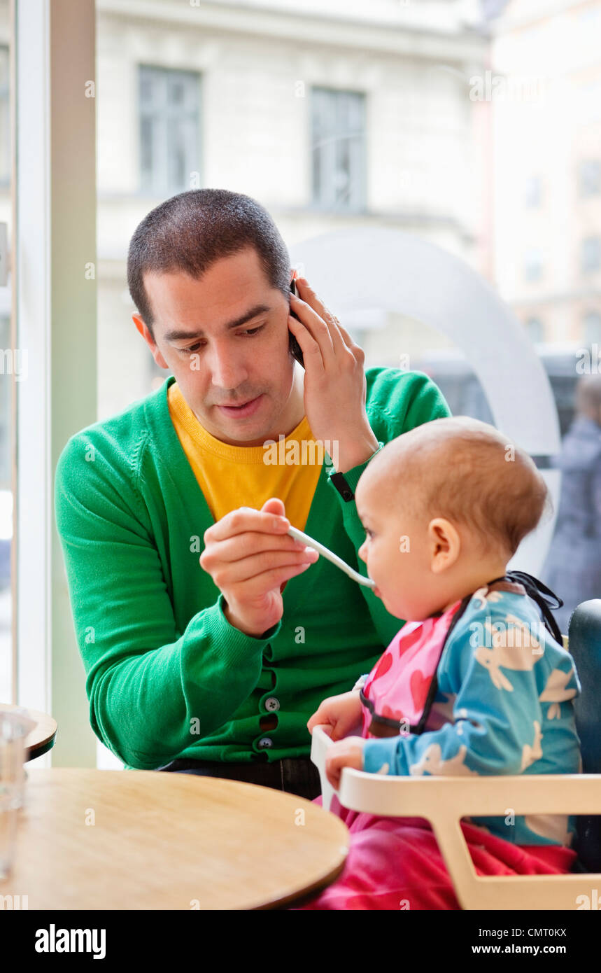Man feeding daughter (0-11 months) and talking in phone - Stock Image