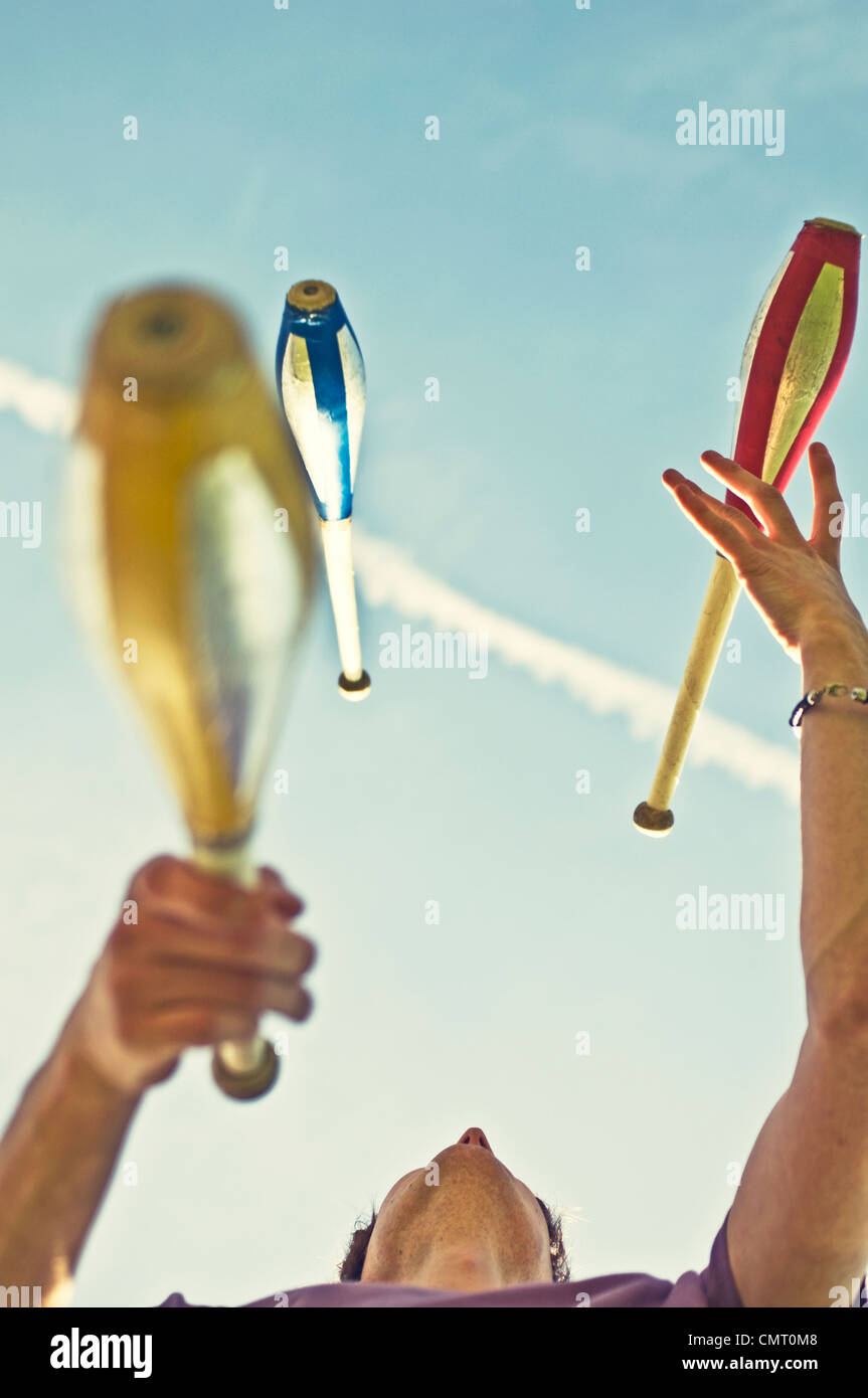 A juggler juggling with clubs - Stock Image