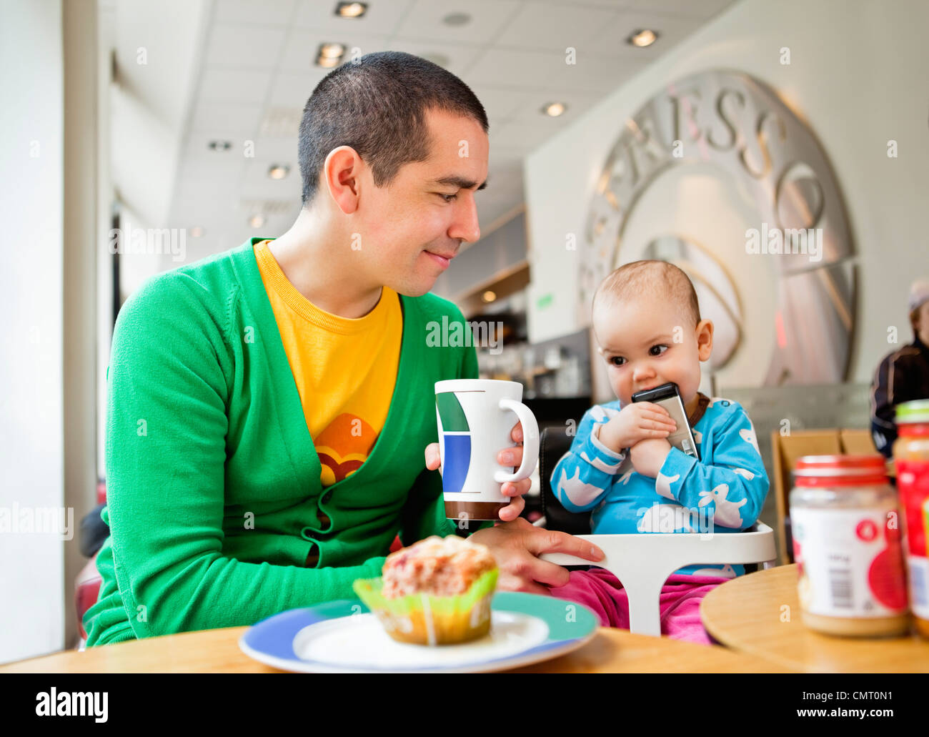 Father and daughter (0-11 months) sitting at coffeehouse - Stock Image