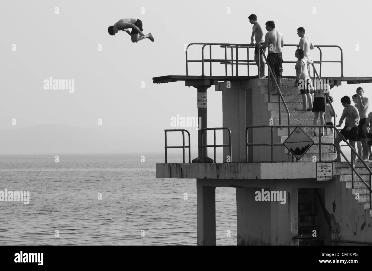 A shot of a man somersaulting off Blackrock diving board while a group of onlookers in bathing suits watch from - Stock Image