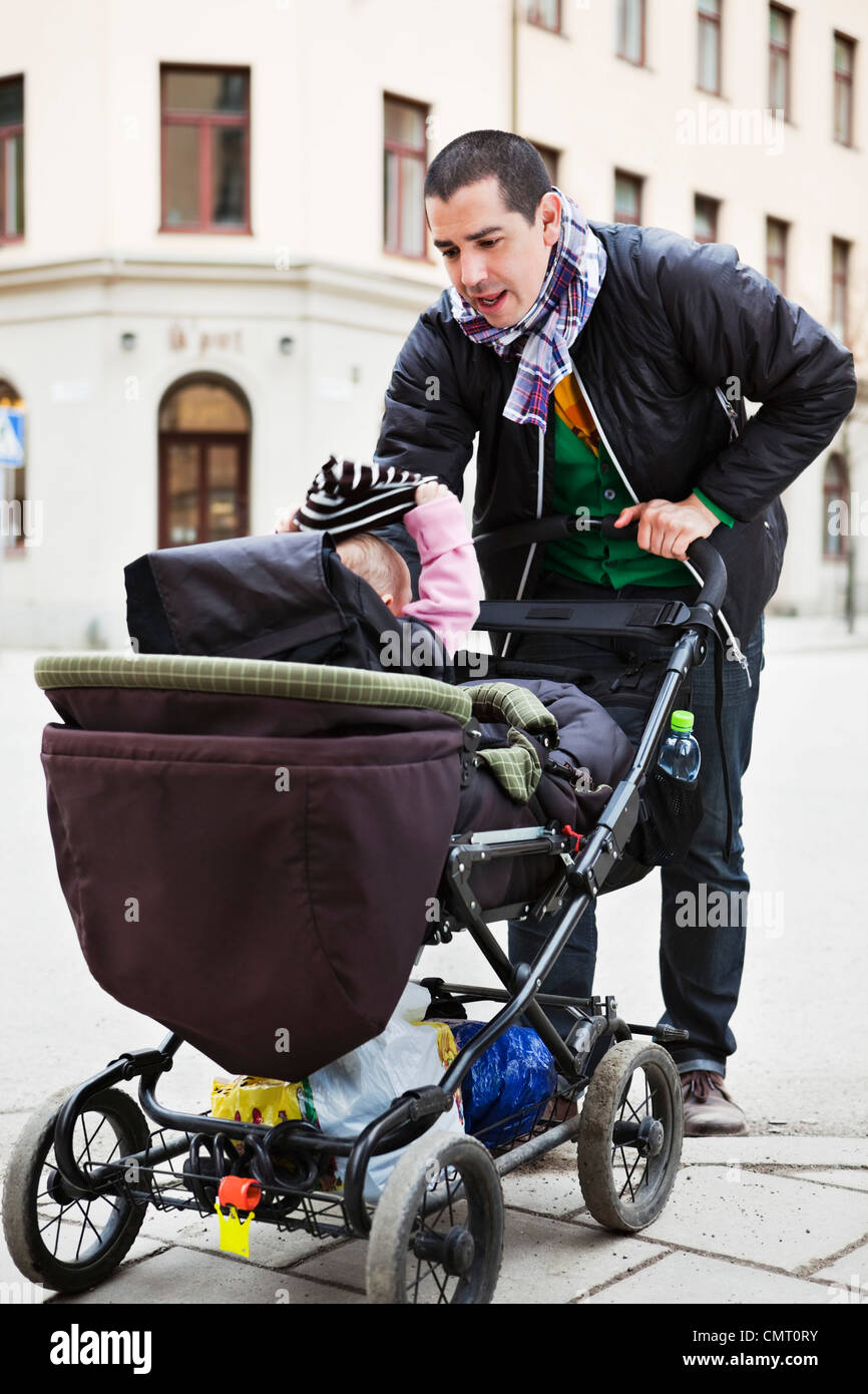 Father with baby (0-11 months) stroller against built structure - Stock Image