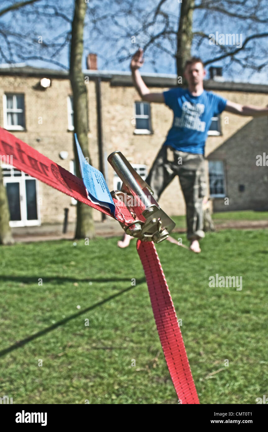 A performer practising on a slackline - Stock Image