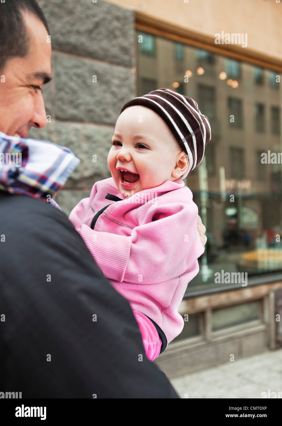Father carrying his happy daughter (0-11 months) - Stock Image