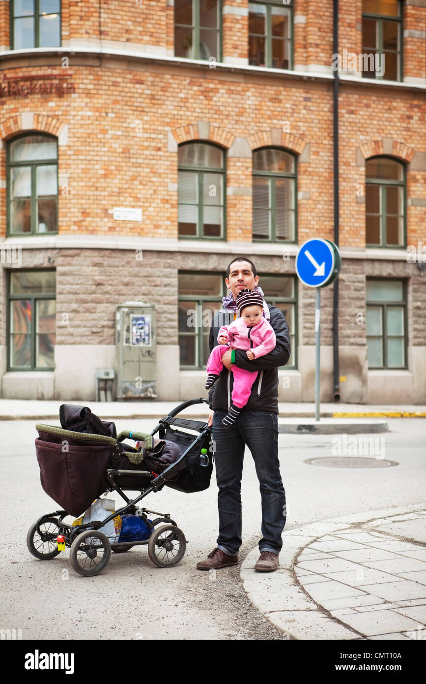 Father and daughter (0-11 months) in downtown with stroller - Stock Image