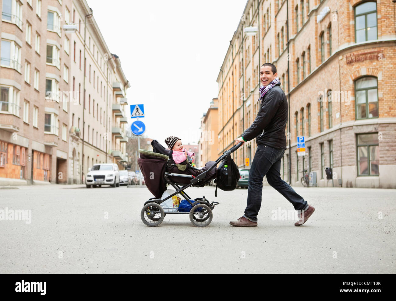 Smiling father walking with cute baby (0-11 months) in stroller - Stock Image