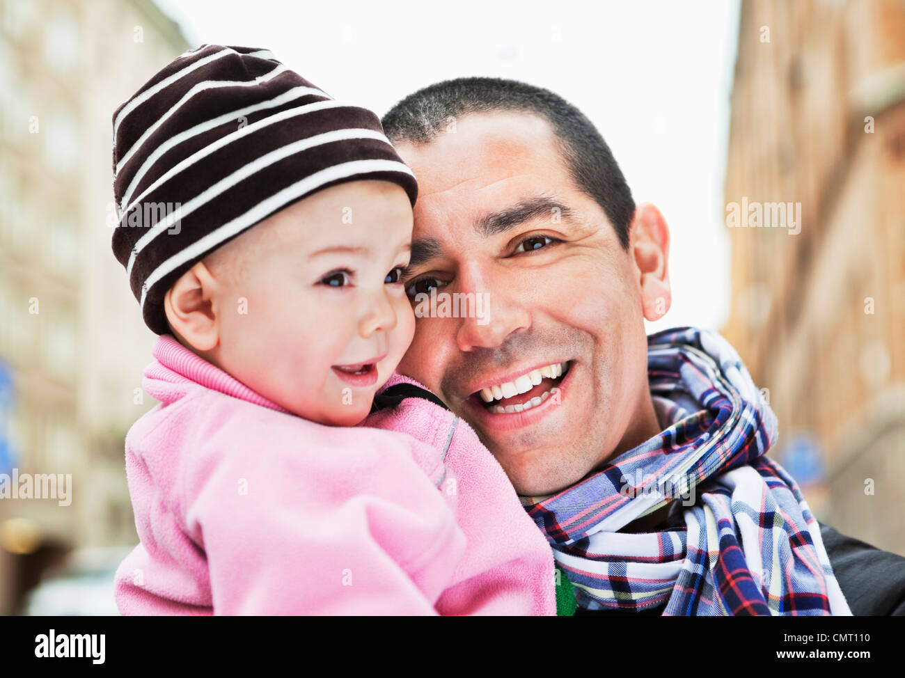 Close-up of smiling father and cute daughter (0-11 months) - Stock Image