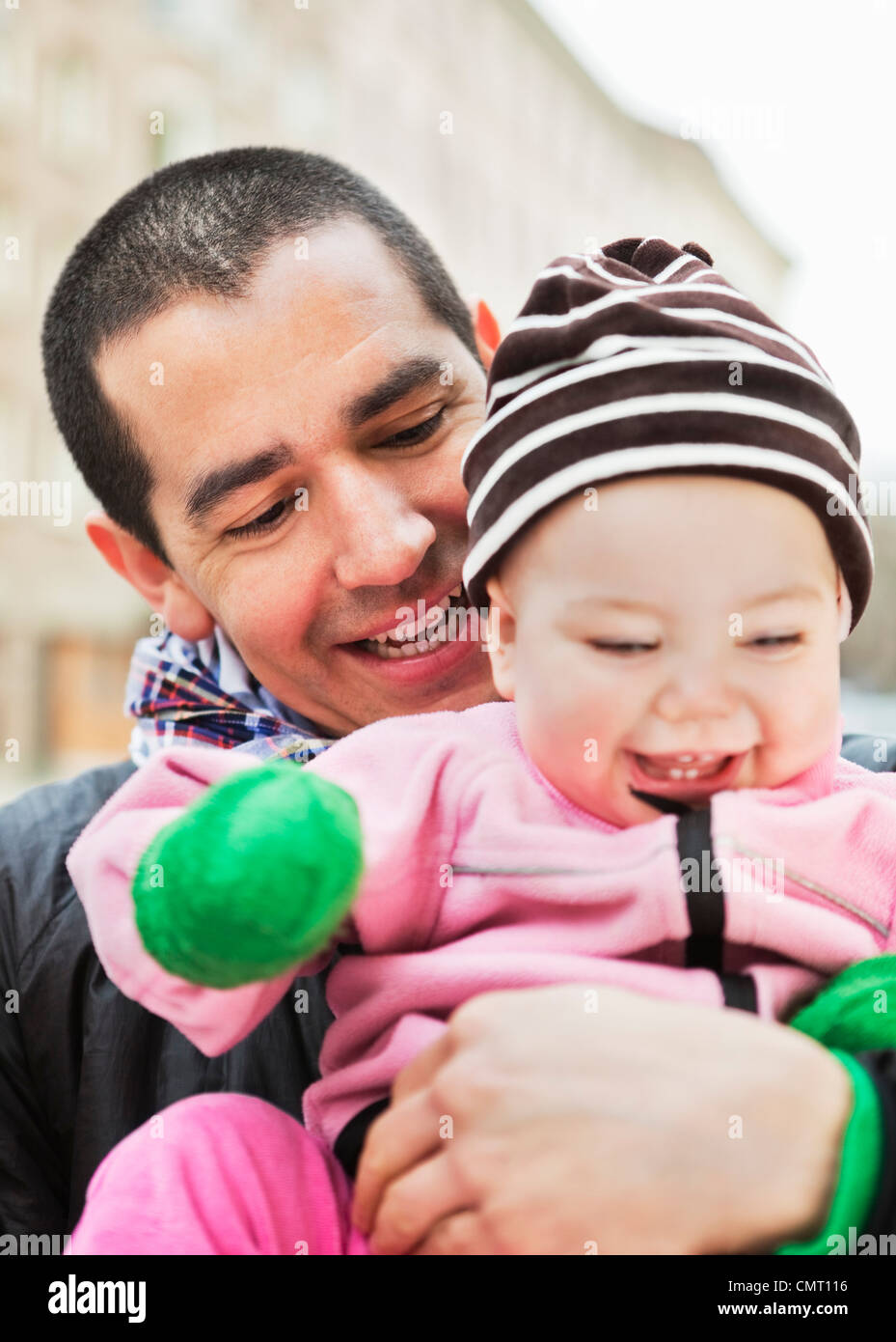 Happy father holding laughing baby (0-11 months) - Stock Image