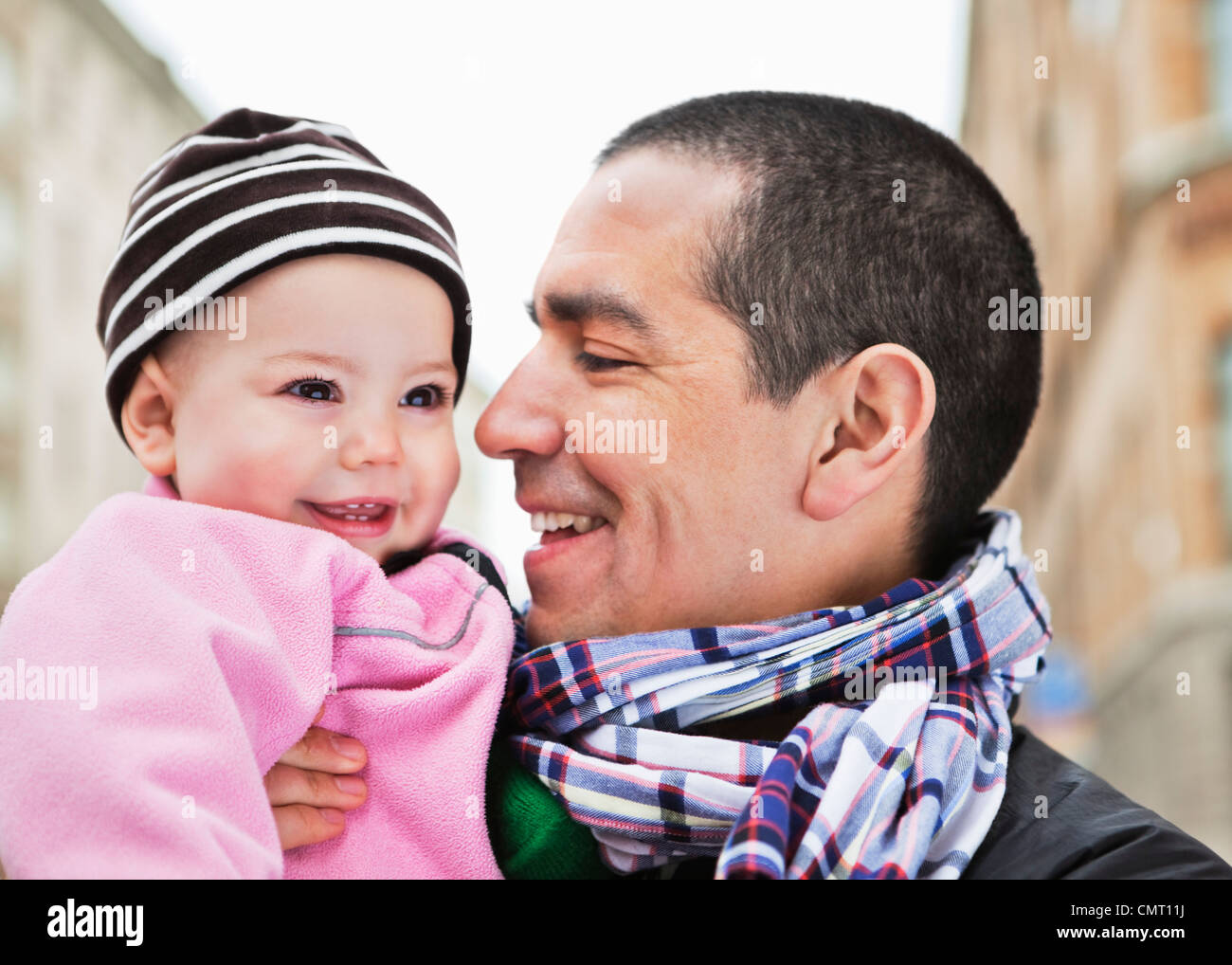 Close-up of father and daughter (0-11 months) smiling - Stock Image