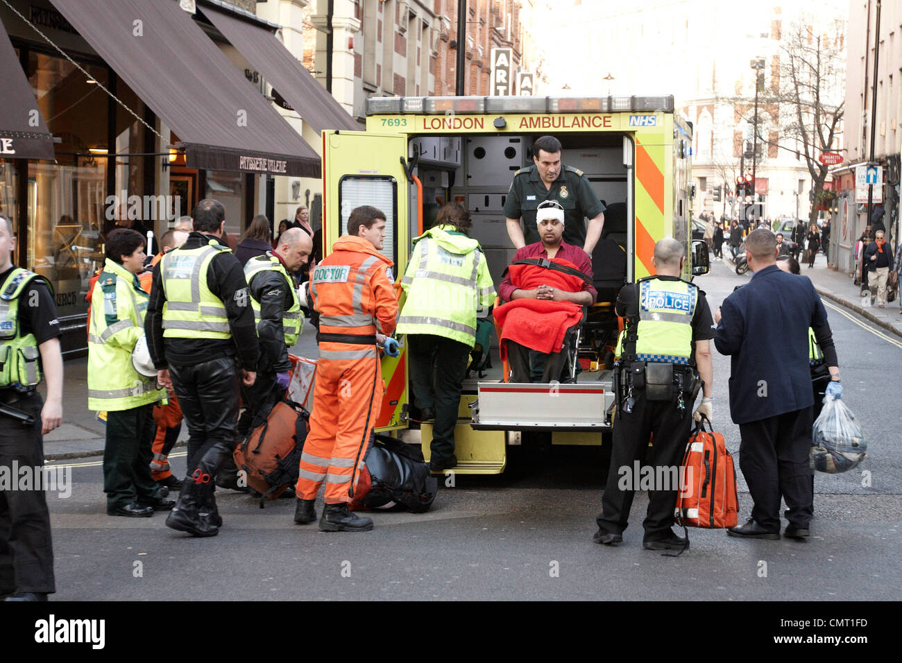 London Ambulance staff treat a male patient outside Leicester Square Tube Station - Stock Image