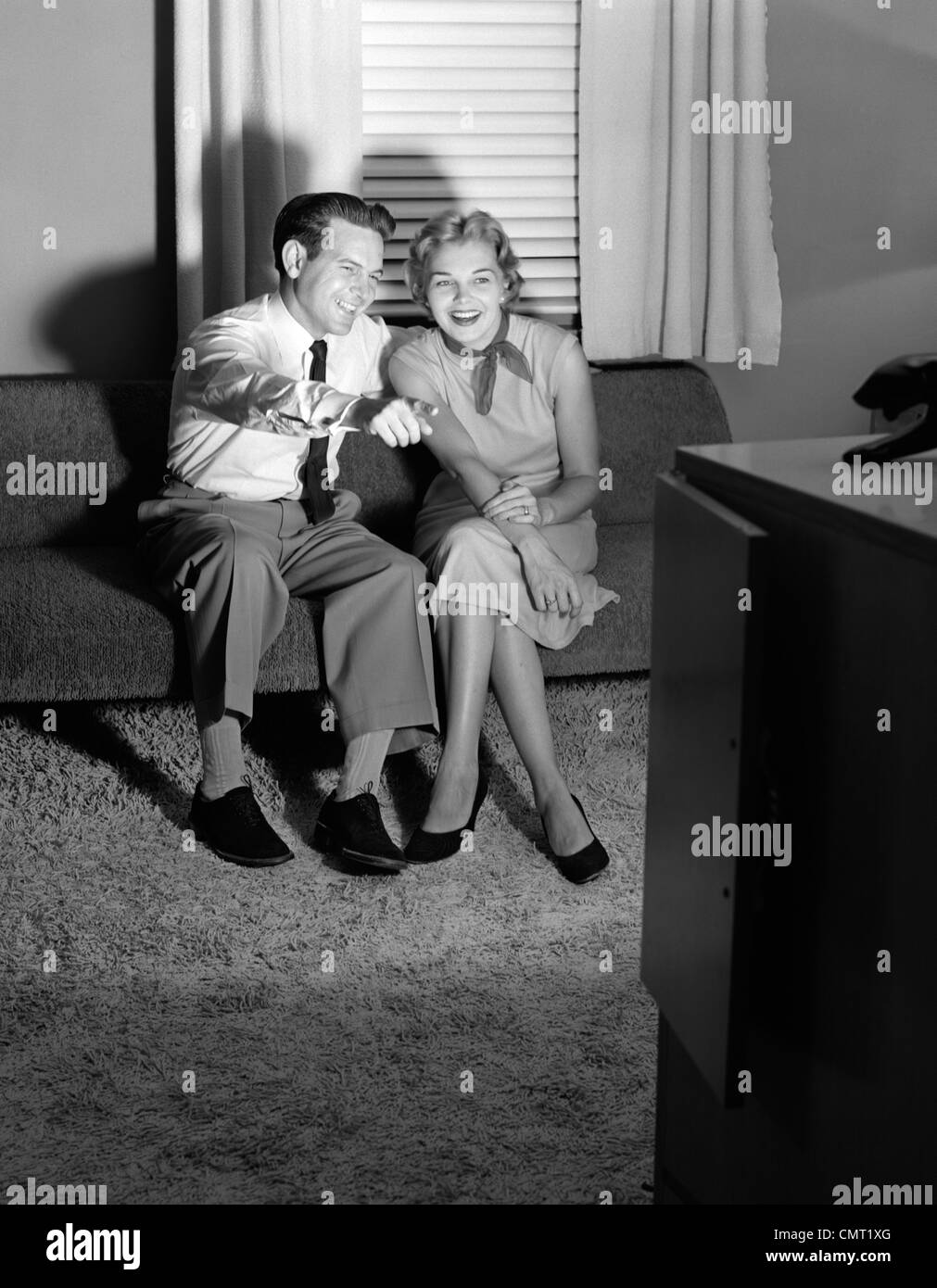 1950s COUPLE IN DARKENED LIVING ROOM WATCHING TV WITH HUSBAND POINTING AT SCREEN - Stock Image