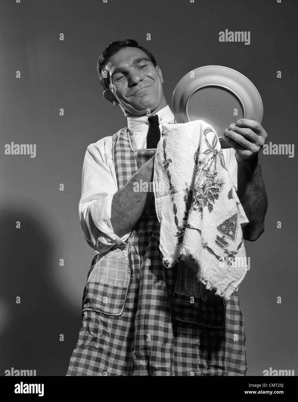 1960s 1950s HUSBAND IN APRON DRYING DISHES - Stock Image